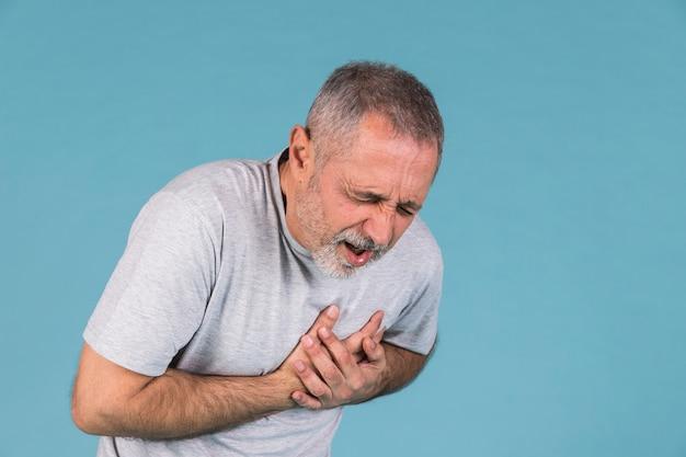 Homem que sofre de dor no peito em pano de fundo azul