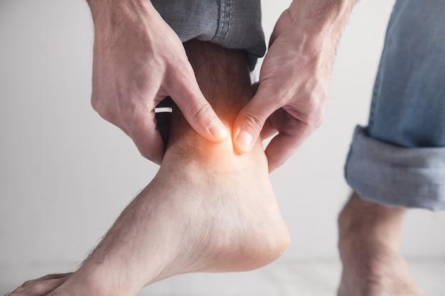 Homem que sofre de dor no tornozelo.