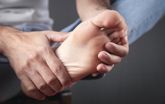 Homem que sofre de dores no pé.