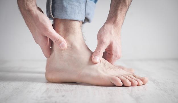 Homem que sofre de dores no tornozelo.