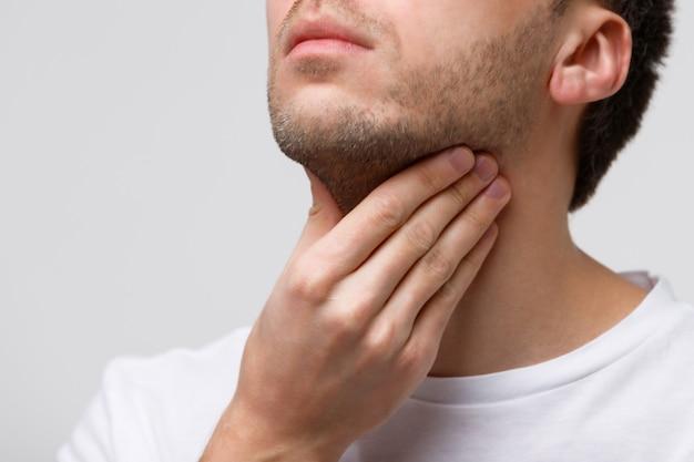 Homem que sofre de problemas na garganta, glândula tireóide, dor ao engolir