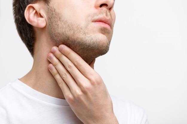 Homem que sofre de problemas na garganta, glândulas linfáticas