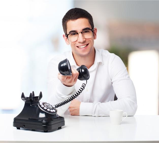 Homem que sorri com um telefone antigo na mão