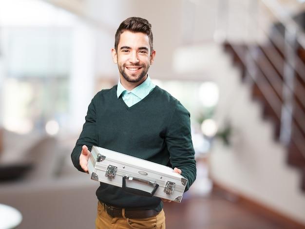 Homem que sorri com uma maleta metálica