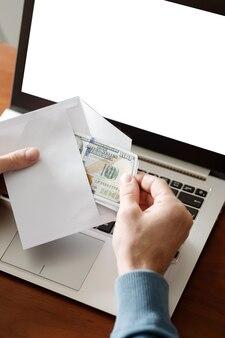 Homem que suborna segurando dinheiro no envelope laptop de atividade financeira ilegal com tela branca