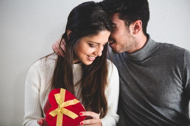 Homem que sussurra algo a sua namorada enquanto ela prende um presente