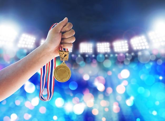 Homem que sustenta uma medalha de ouro contra, conceito da vitória.