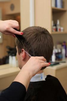 Homem que tem um corte de cabelo de cabeleireiro.