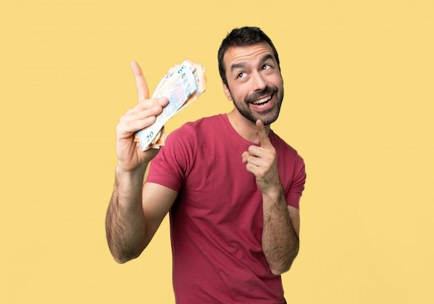Homem que toma muito dinheiro que aponta com o indicador e que olha acima no fundo amarelo isolado