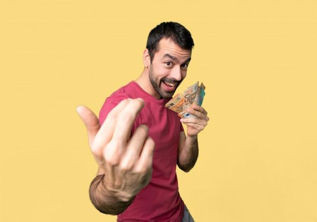 Homem que toma muito dinheiro que convida para vir com mão. feliz que você veio no fundo amarelo isolado