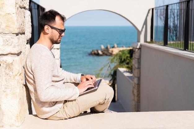 Homem que trabalha ao ar livre perto da praia