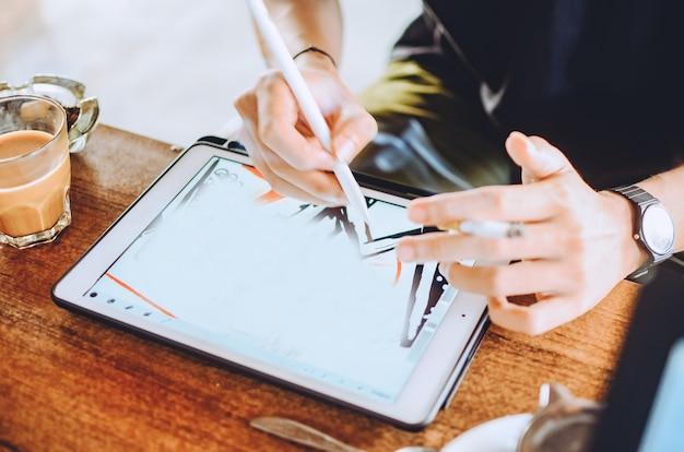 Homem que trabalha com computador tablet portátil. designer que desenha o plano digital em um escritório moderno e leve. horizontal. fundo desfocado.