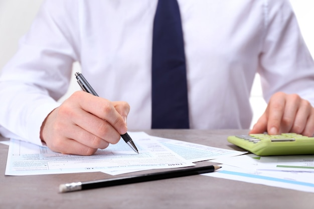 Homem que trabalha com documentos e calculadora.