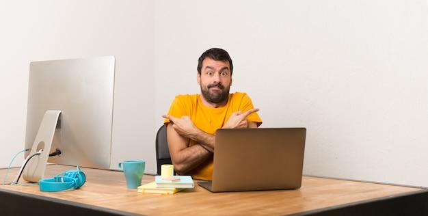 Homem que trabalha com laptot em um escritório apontando para as laterais tendo dúvidas