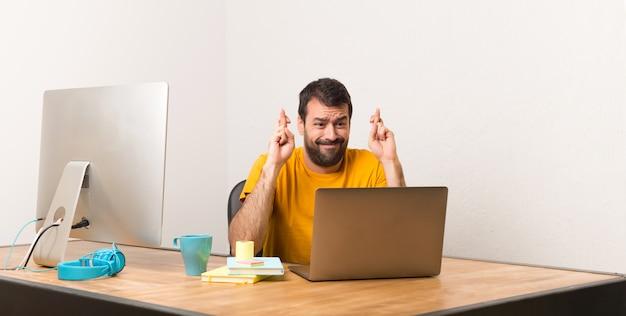 Homem que trabalha com laptot em um escritório com os dedos cruzando e desejando o melhor
