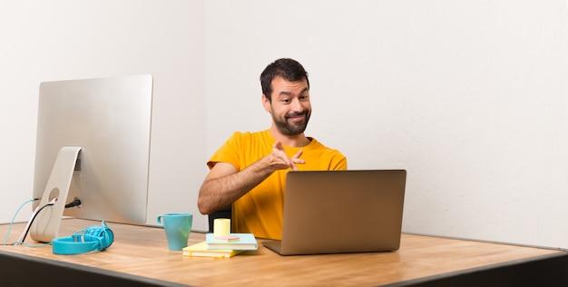 Homem que trabalha com laptot em um escritório, estendendo as mãos para o lado para convidar para vir