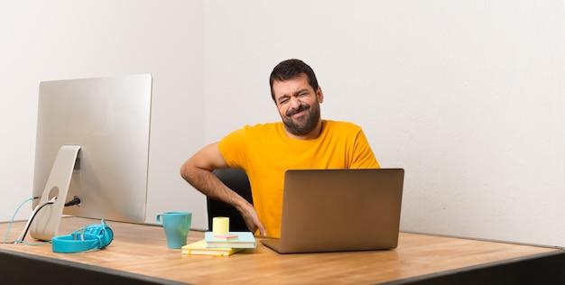 Homem que trabalha com laptot em um escritório que sofre de dor nas costas por ter feito um esforço