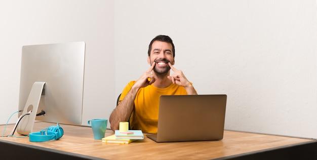 Homem que trabalha com laptot em um escritório, sorrindo com uma expressão feliz e agradável