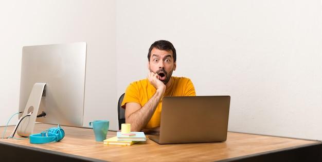 Homem que trabalha com laptot em um escritório surpreso e chocado ao olhar para a direita