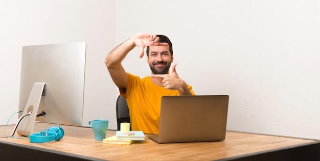 Homem que trabalha com laptot em uma face de focalização do escritório. símbolo de enquadramento