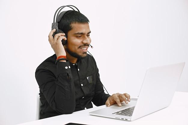 Homem que trabalha com o laptop. expedidor indiano ou trabalhador de linha direta.
