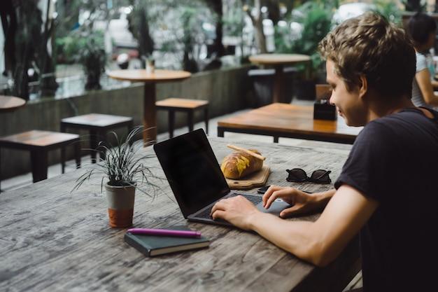 Homem que trabalha com um laptop em um café em uma mesa de madeira