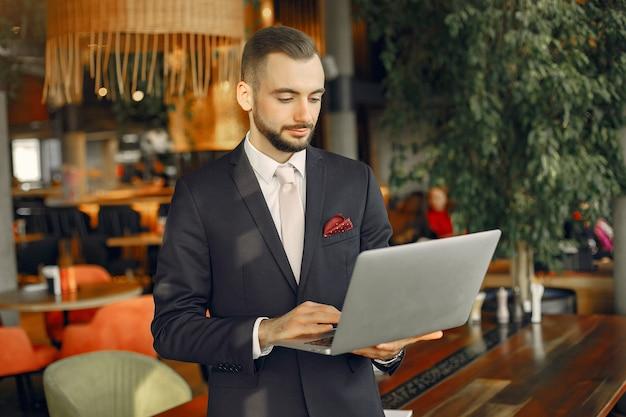 Homem que trabalha com um laptop na mesa