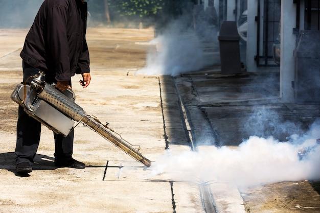 Homem que trabalha com uma máquina de fumaça no bueiro para controle de pragas