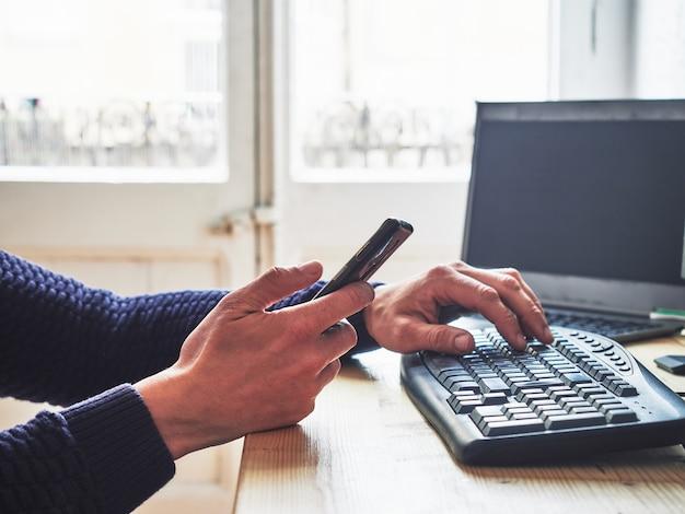 Homem que trabalha em casa com seu computador e telefone na mão