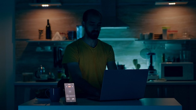 Homem que trabalha em casa com sistema de iluminação de automação, sentado na cozinha, acendendo as luzes usando o comando de voz para o aplicativo de casa inteligente no smartphone. pessoa monitorando luz com dispositivo wi-fi