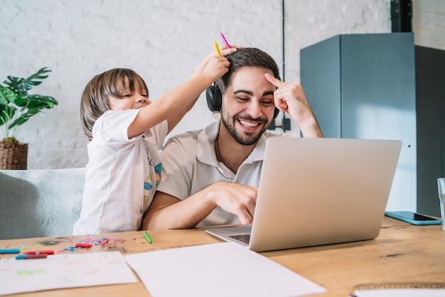 Homem que trabalha em casa, cuidando de seu filho. ficar em casa. trabalhando em casa durante a quarentena covid-19.
