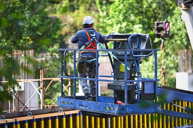 Homem que trabalha em elevadores de carga em uma construção.