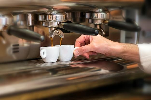 Homem que trabalha em uma casa de café preparando café expresso