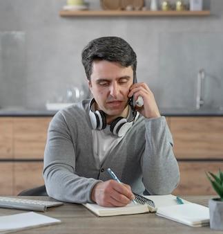Homem que trabalha na área de mídia, atendendo uma ligação e escrevendo coisas no caderno