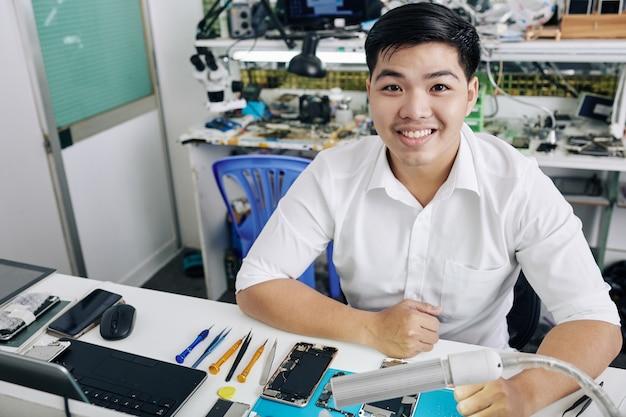 Homem que trabalha na loja de reparo do smartphone