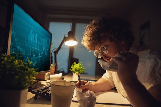 Homem que trabalha no escritório sozinho durante o coronavírus ou a quarentena de covid-19, ficando até tarde da noite