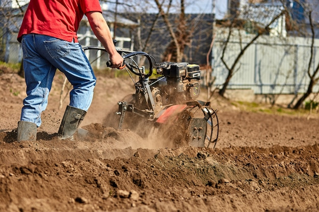 Homem que trabalha no jardim com rebento de jardim. rebento de jardim para trabalhar, close-up. homem com trator, cultivando o campo na primavera.