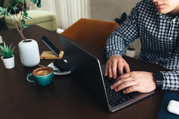 Homem que trabalha no laptop com uma xícara de café e bolo de chocolate, telefone, planta. foto de alta qualidade