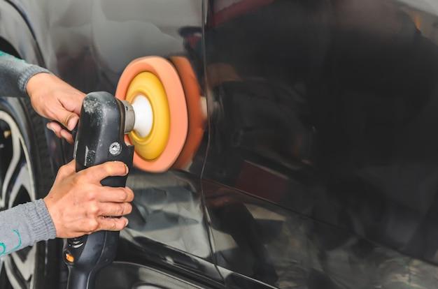 Homem que trabalha para o polimento, revestimento de carros.