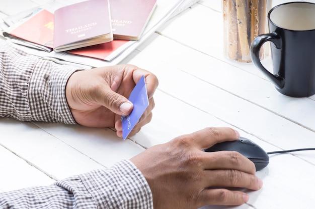 Homem que usa o cartão de crédito para o pagamento que compra em linha em torno do curso e da viagem.