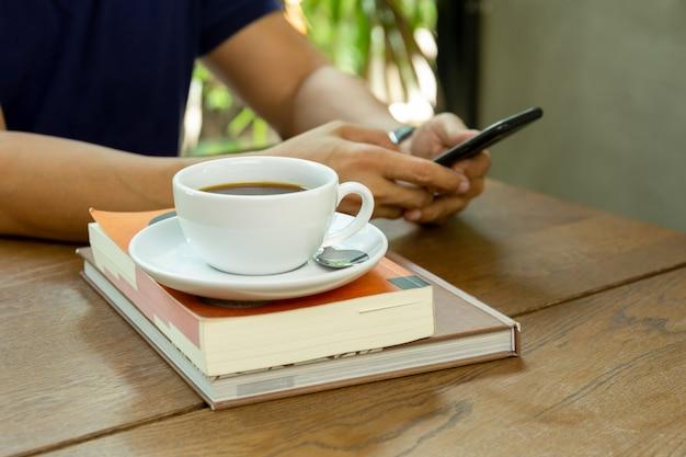 Homem que usa o telefone celular com a xícara de café na tabela no café.