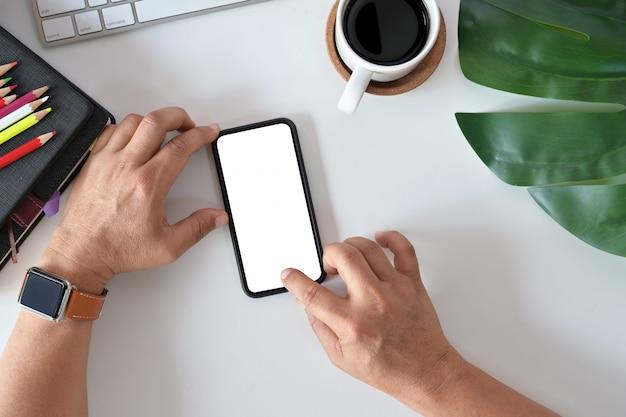Homem que usa o telefone celular no escritório. tela em branco para montagem de exibição