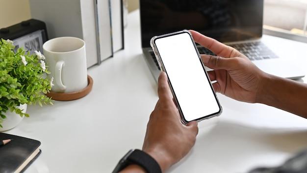 Homem que usa o telefone móvel do modelo na mesa de escritório com exposição do trajeto de grampeamento.