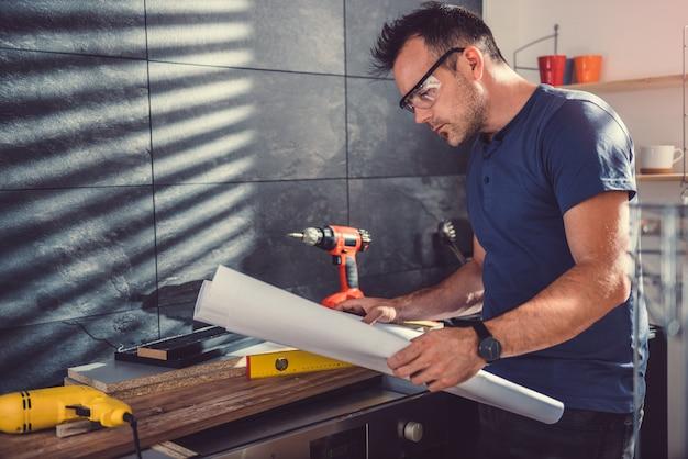 Homem que verifica plantas ao construir armários de cozinha