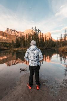 Homem que viaja em pé aprecia a paisagem do reflexo das montanhas three sisters no rio no outono em canmore, canadá