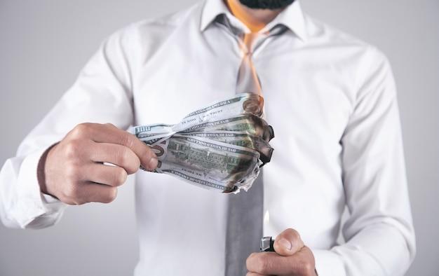 Homem queimando notas de dólar.