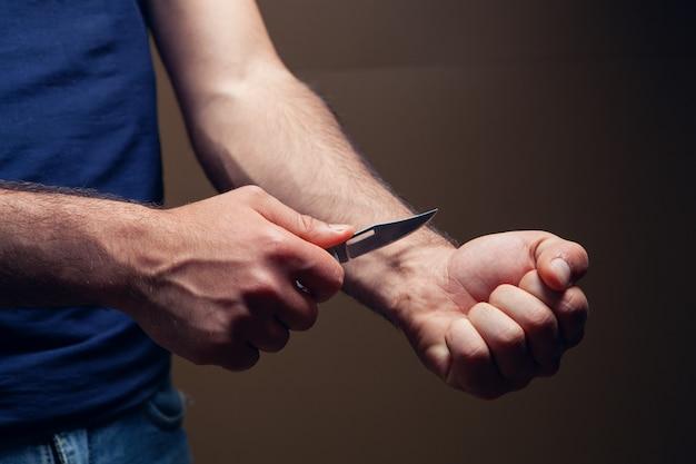 Homem quer cortar veias em fundo marrom