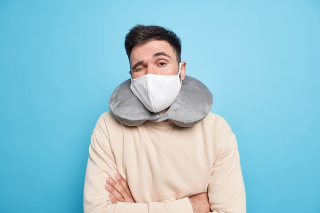 Homem quer descansar mantém os braços cruzados usa máscara protetora durante poses de travesseiro inflado de pescoço pandêmico de coronavírus em jumper casual