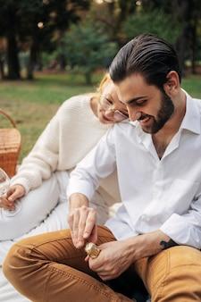 Homem querendo abrir uma garrafa de vinho ao lado de sua esposa