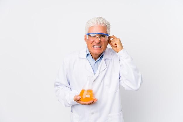 Homem químico maduro isolado cobrindo as orelhas com as mãos.